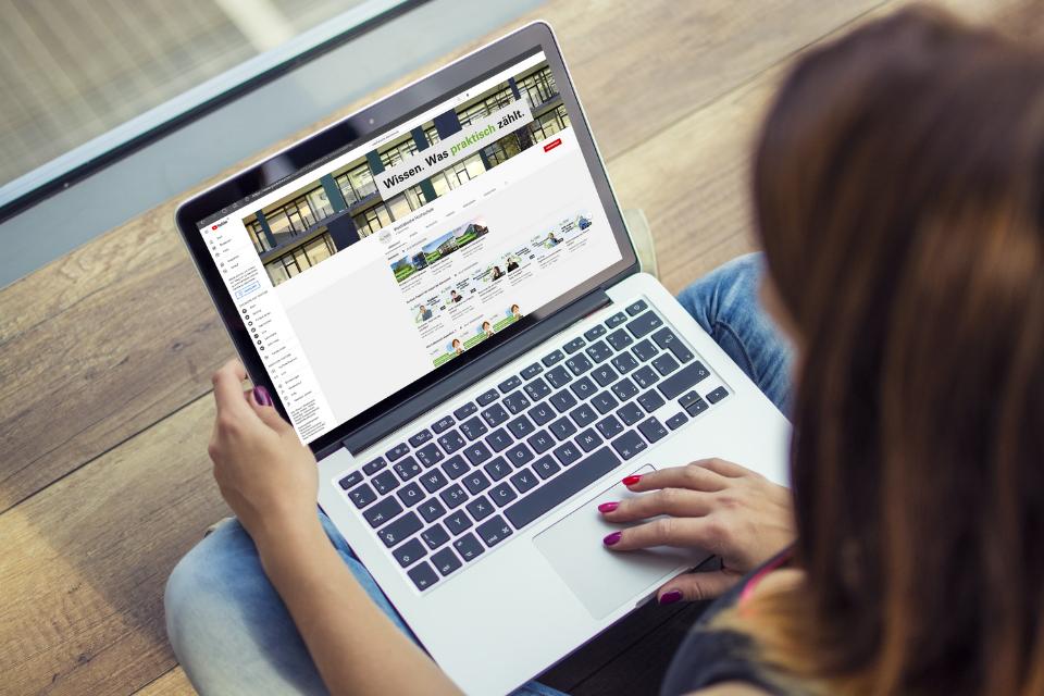 Man schaut einer Frau über die Schultern, die einen Laptop auf dem Schoß hat. Auf dem Bildschirm sieht man die Kanalansicht des neuen WH-Youtube-Kanals.