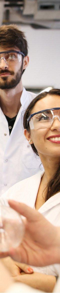 Zwei Studierende in Laborkitteln und mit Schutzbrille.