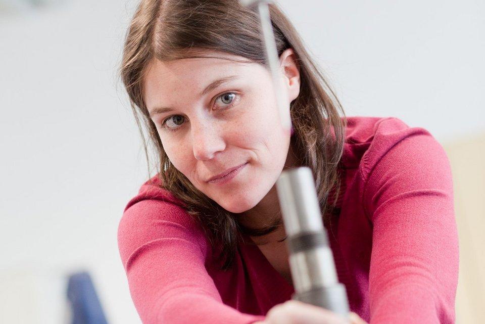 Braunhaariges Mädchen arbeitet konzentriert an einer technischen Maschine