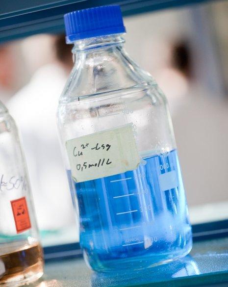 Nahaufnahme einer blauen Flüssigkeit in einer, mit einer chemischen Formel beschrifteten, Schraubverschluss-Glasflasche.