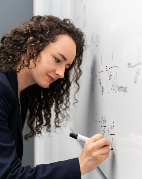 Eine Frau mit lockigen, schwarzen Haaren steht gebeugt vor einem Whiteboard und schreibt Formeln auf