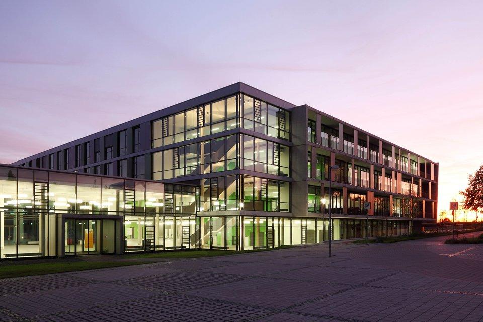 Grün beleuchtete Gebäude des Campus Gelsenkirchen bei Nacht.