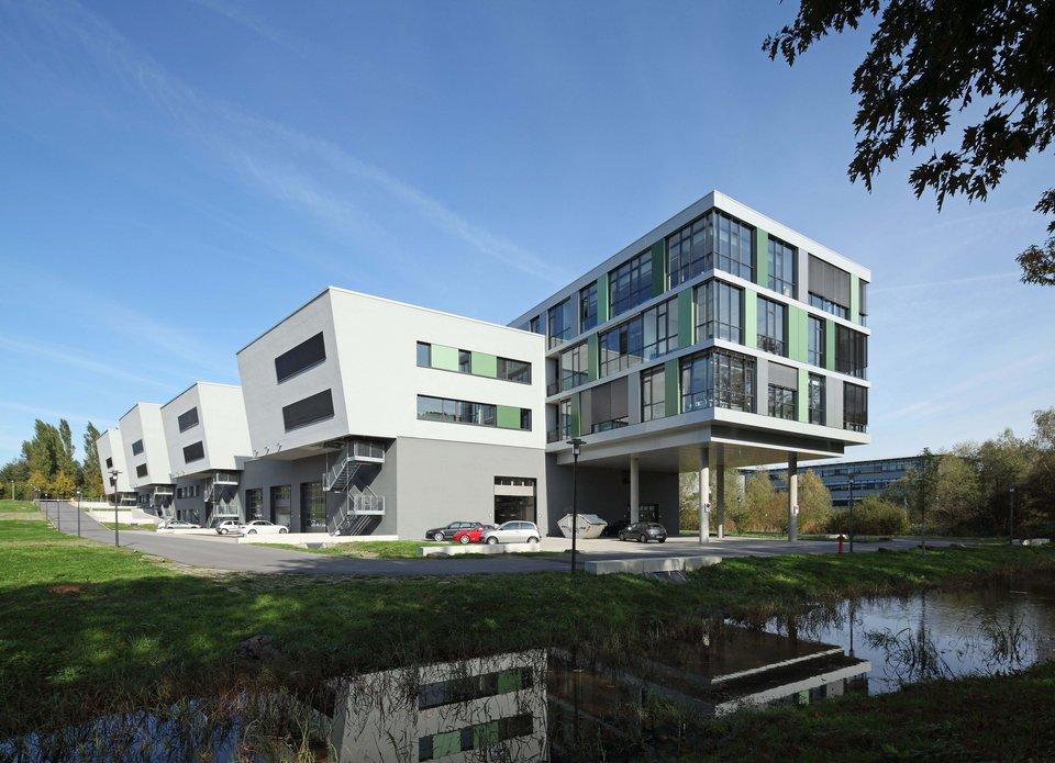 Rückansicht des Campusgebäude inklusive des kleinen Sees.