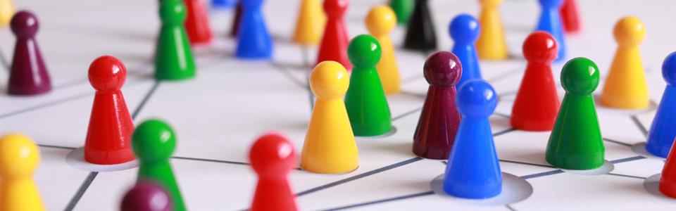 Bunte Brettspielfiguren auf einem Spielfeld.
