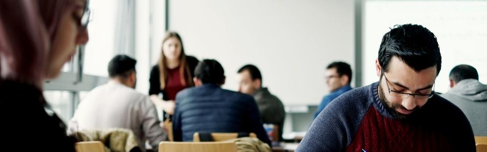 Studierende sitzen an Tischen in der Hochschule