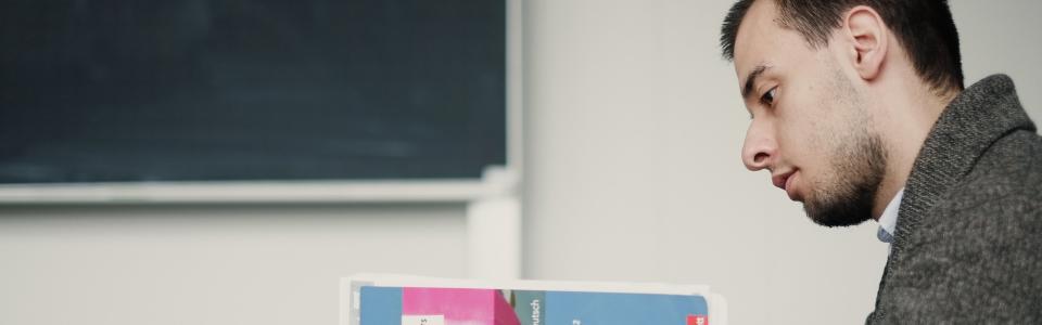 Studierender liest das Deutsch Arbeitsbuch