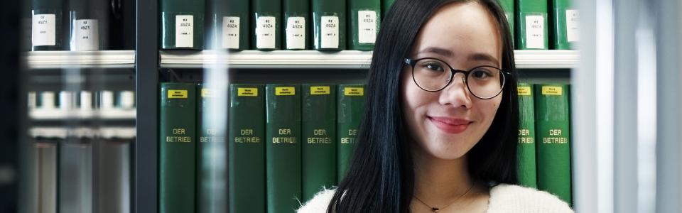 Internationale Studierende lächelt in die Kamera in der Bibliothek