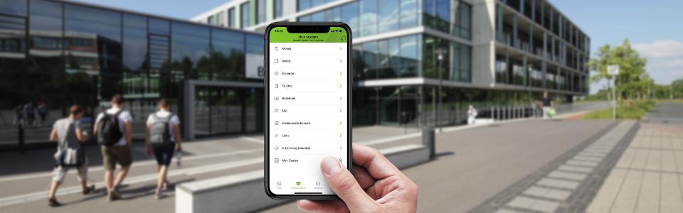 Hand hält Smartphone mit geöffneter UniNow-App. Im Hintergrund sind Studierende und der Campus Gelsenkirchen verschwommen zu sehen.