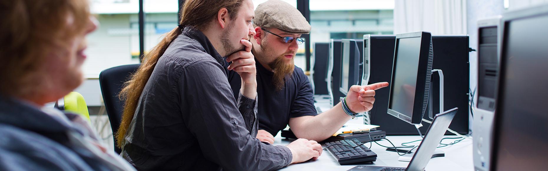 Zwei junge Männer sitzen vor einem Computer und schauen auf den Monitor.