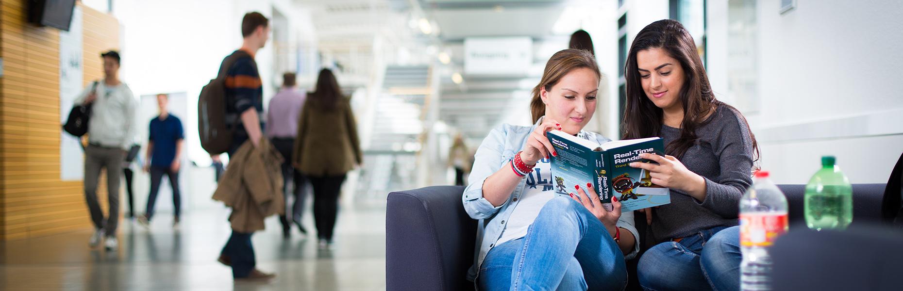Zwei junge Frauen sitzen auf einer Couch und schauen gemeinsam in ein Fachbuch für Medieninformatik.